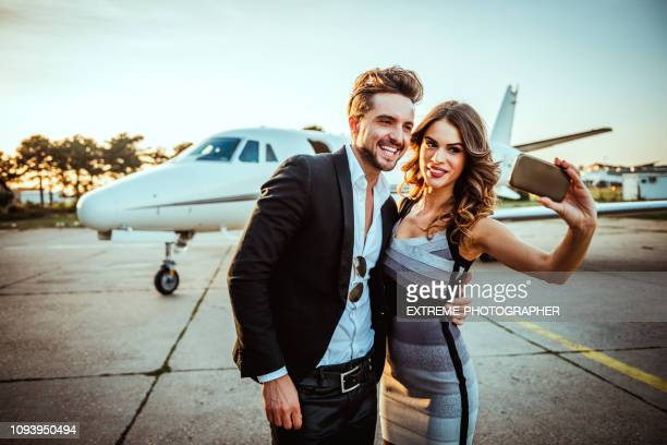rich and famous couple taking a selfie for social media while embracing each other in front of a private airplane parked on a tarmac - influencer stock pictures, royalty-free photos & images