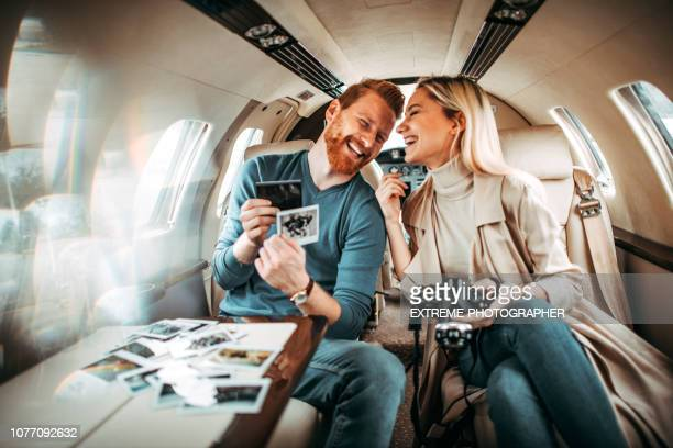 rich and successful young tourist couple sitting inside a private airplane and laughing while looking at photographs - private stock pictures, royalty-free photos & images