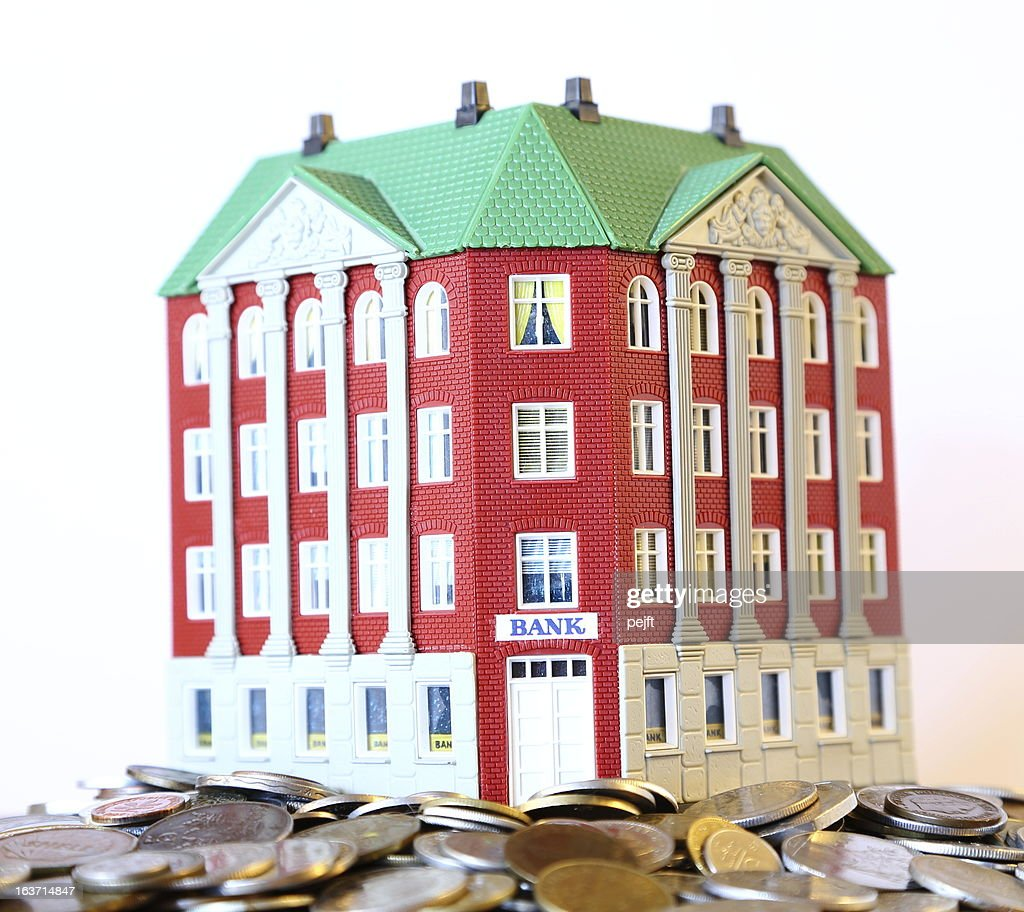 Rich Bank building on money and coins : Stock Photo
