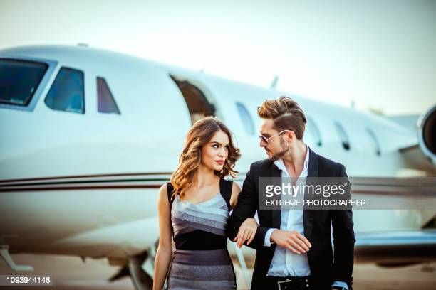 rich business couple walking together with hands crossed in front of a private jet parked on a taxiway - glamour stock pictures, royalty-free photos & images