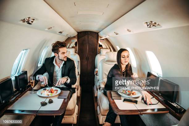 rich entrepreneur couple having a meal aboard a private airplane - side by side stock pictures, royalty-free photos & images