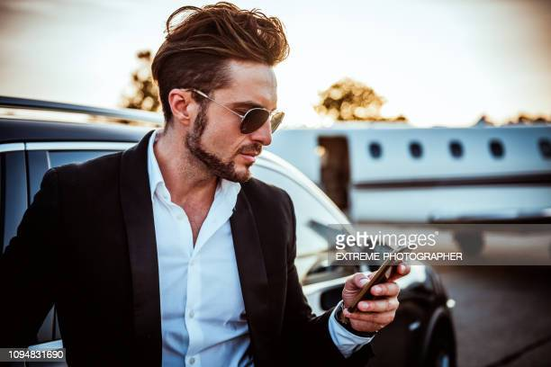 rich entrepreneur using a mobile phone with a luxurious black car and a private jet parked behind him - prestige car stock pictures, royalty-free photos & images