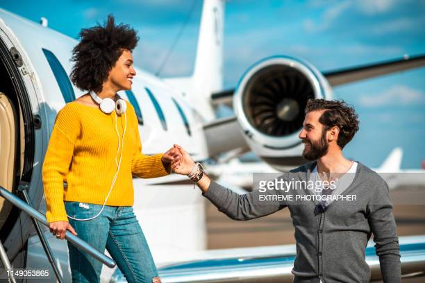 rich gentleman holding his partner's hand as she's exiting a parked private airplane - charming stock pictures, royalty-free photos & images