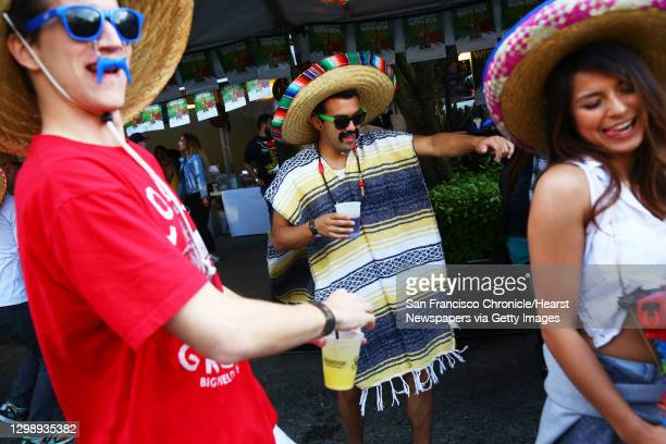 Rich Goodloe, left, Kenzo Kressbach, center, and Samantha Lee dance at the annual Cinco de Mayo block party hosted by the Green Lake Tacos Guaymas,...