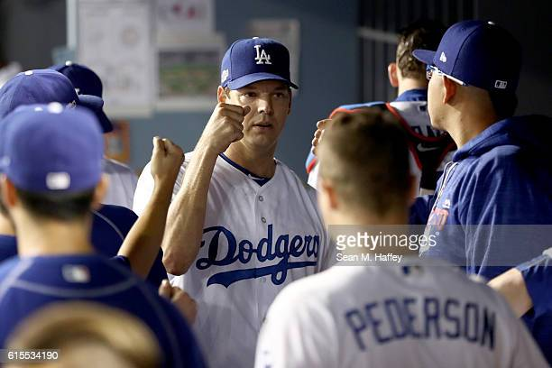 Rich Hill of the Los Angeles Dodgers is greeted by teammates in the dugout while taking on the Chicago Cubs in game three of the National League...