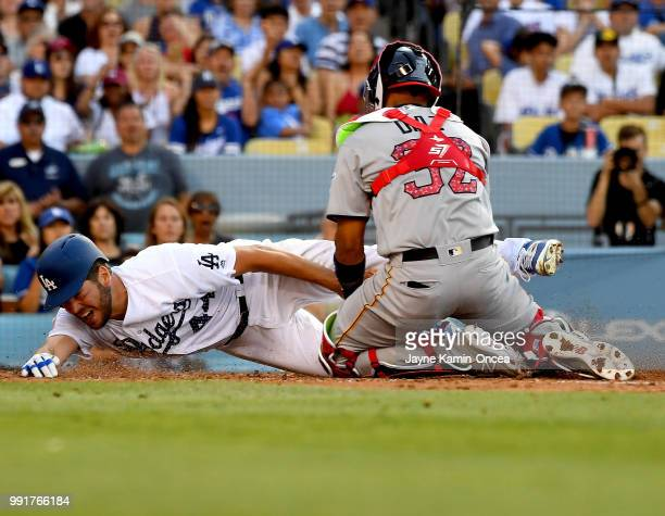 Rich Hill of the Los Angeles Dodgers is tagged out at home by Elias Diaz of the Pittsburgh Pirates attempting to tag up from third base on a fly ball...