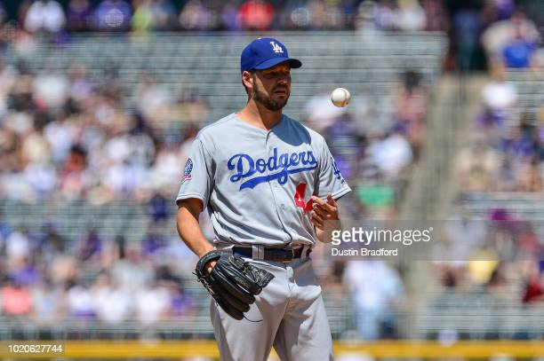 Rich Hill of the Los Angeles Dodgers tosses the ball as he pitches against the Colorado Rockies in the first inning of a game at Coors Field on...