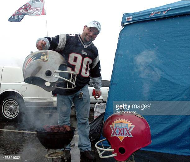 Rich Lefevere of Dery NH lifts the helmet off his beef tritips in front of Gillette Stadium prior to the start of the AFC Championship Game on...