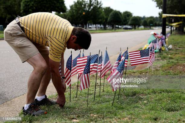 Rich Lindgren places 12 US flags in the ground at a makeshif memorial outside of the crime scene at the Virginia Beach Municipal Center June 01 2019...