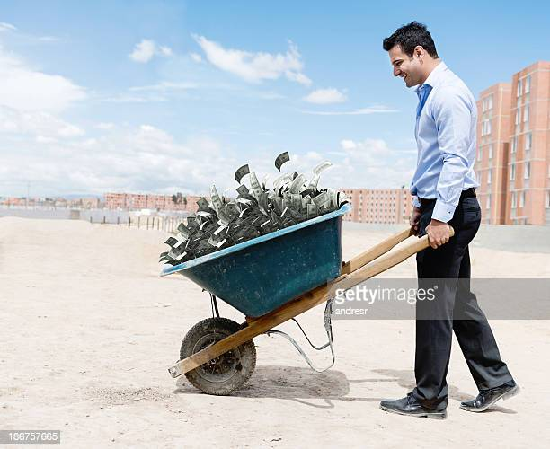 rich man carrying money - wheelbarrow stock photos and pictures