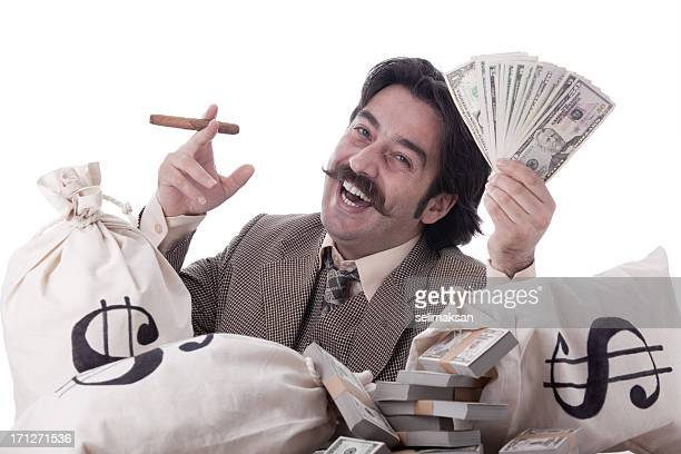 rich man posing with money bags and dollar bills - ebenezer scrooge stock photos and pictures