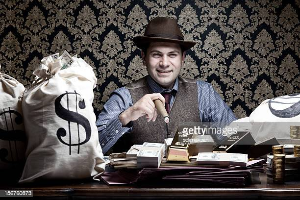 Rich man posing with money bags, gold and dollar bills
