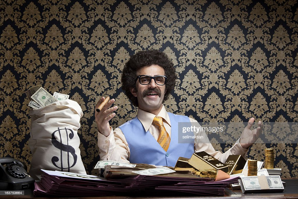 Rich man posing with money bags, gold bullions, dollar bills : Stockfoto