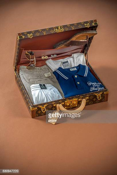rich man's vacation suitcase on brown backdrop - louis vuitton designer label stock pictures, royalty-free photos & images