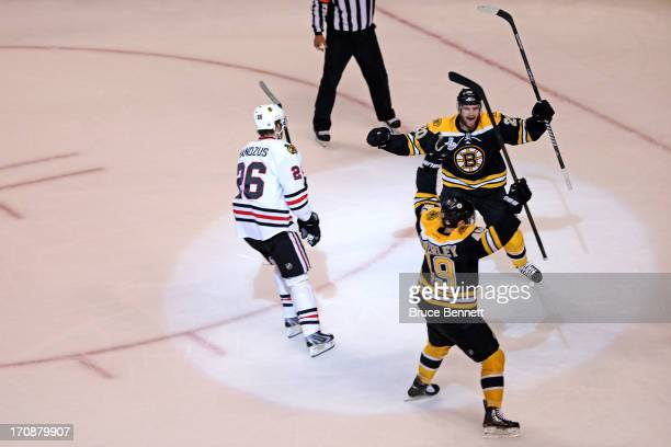 Rich Peverley of the Boston Bruins celebrates with Daniel Paille after scoring a goal as Michal Handzus of the Chicago Blackhawks looks on during the...