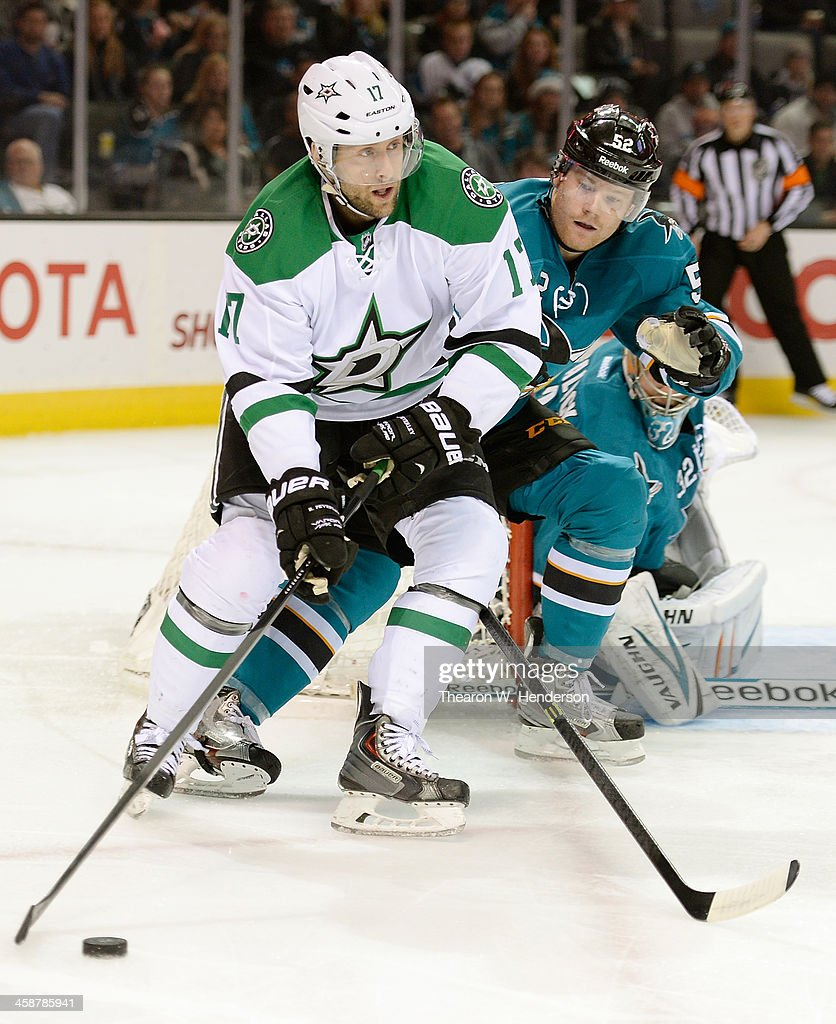 Rich Peverley #17 of the Dallas Stars skates with control of the puck from behind the net, defended by Matt Irwin #52 of the San Jose Sharks during the first period at SAP Center on December 21, 2013 in San Jose, California.