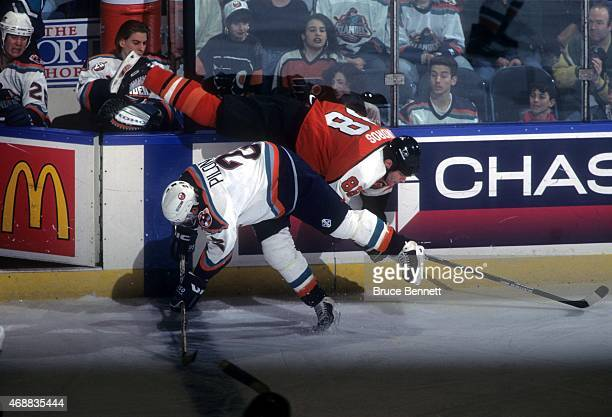 Rich Pilon of the New York Islanders checks Eric Lindros of the Philadelphia Flyers into the boards during their game on March 22 1997 at the Nassau...