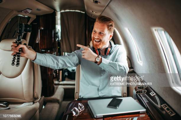 rich redhead man shooting a video blog while traveling on a private jet - camera icon stock pictures, royalty-free photos & images