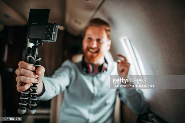 Rich redhead social media icon shooting a vlog while traveling on a private jet