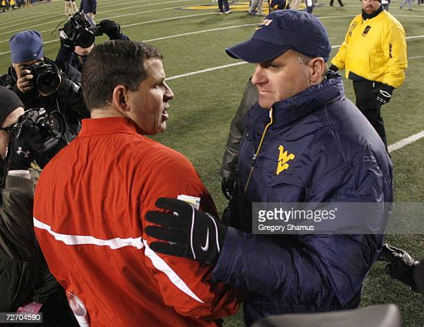Rich Rodriguez head coach of the Virginia Mountaineers shakes the hand of Greg Schiano head coach of the Rutgers Scarlet Knights after a 41-39 West...