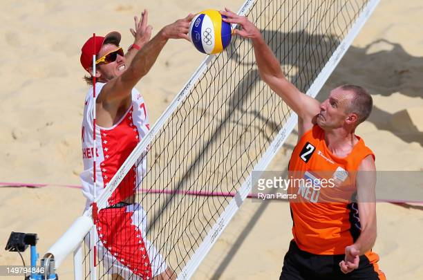 Rich Schuil of Netherlands and Patrick Heuscher of Switzerland contest the ball at the net during the Men's Beach Volleyball Round of 16 match...