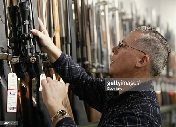 Rich Vance, co-owner of Vance's gun store, selects a Remington rifle from the gun display in Columbus, Ohio, omn Thursday, April 5, 2007. Remington...