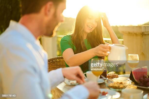 rich young couple enjoying breakfast on terrace