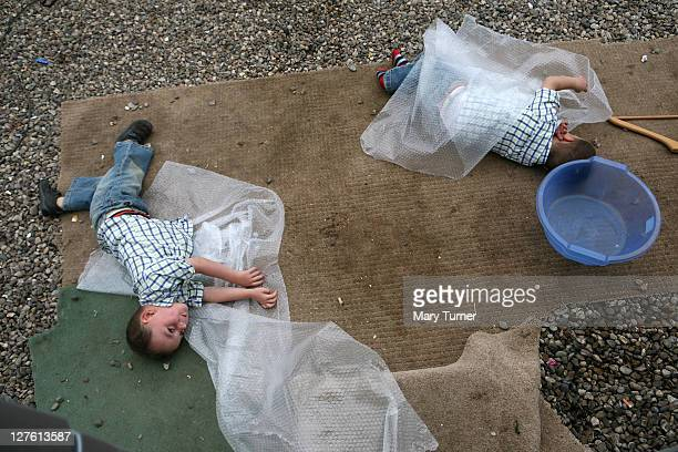 Richard and John 'Button' Sheridan aged 2 play with bubblewrap outside their caravan at Dale Farm on September 4 2011 near Basildon England Hundreds...
