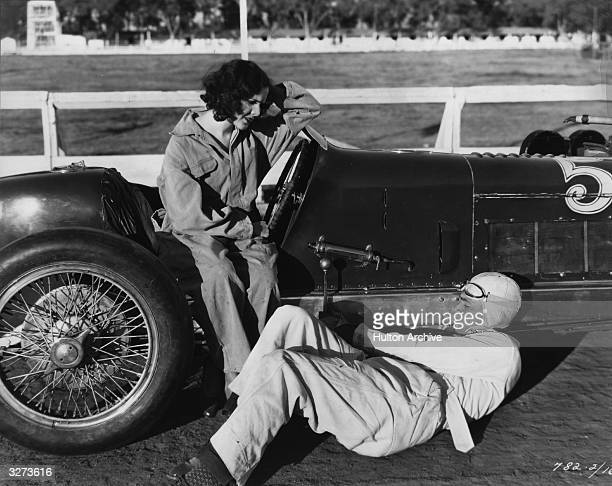 Richard Arlen examines the underside of his racing car watched from the driving seat by actress Mary Brian in a scene from 'Burning Up' directed by A...