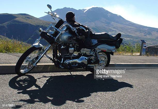Richard Arthur of Rainier, Oregon, watches steam rise from the crater of Mount St. Helens, as he sits on his motorbike October 14, 2004 at Clearwater...