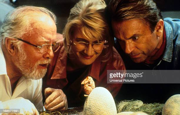 Richard Attenborough, Laura Dern and Sam Neill watch a hatching in a scene from the film 'Jurassic Park', 1993.