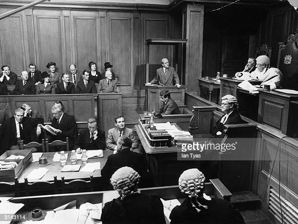 Richard Attenborough stands in the dock playing John Reginald Christie in the film 10 Rillington Place Andre Morell plays Judge Lewis in the true...