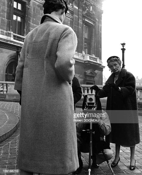 Richard Avedon during a shooting session with Carmel Snow editor of the American edition of Harper's Bazaar and a Dior model in front of the Opera de...