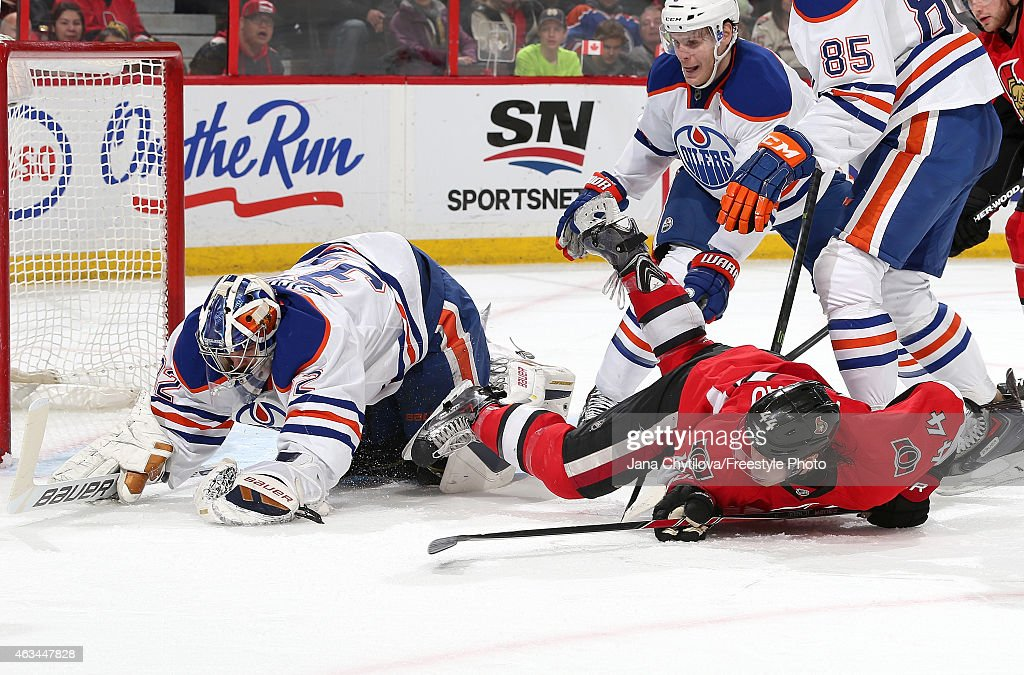 Richard Bachman #32 of the Edmonton Oilers makes a save against a falling Jean-Gabriel Pageau #44 of the Ottawa Senators in the second period at Canadian Tire Centre on February 14, 2015 in Ottawa, Ontario, Canada.