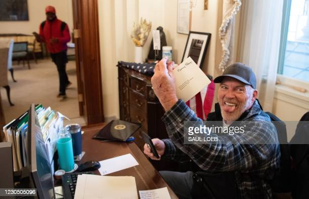 Richard Barnett, a supporter of US President Donald Trump, holds a piece of mail as he sits inside the office of US Speaker of the House Nancy Pelosi...