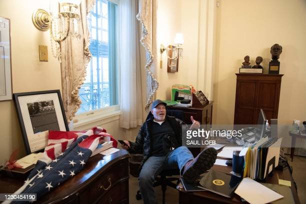 Richard Barnett, a supporter of US President Donald Trump sits inside the office of US Speaker of the House Nancy Pelosi as he protest inside the US...