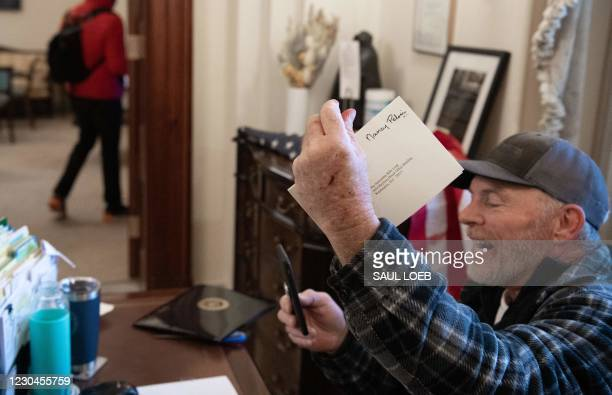Richard Barnett, a supporter of US President Donald Trump sits inside the office of Speaker of the House Nancy Pelosi as he protests inside the US...