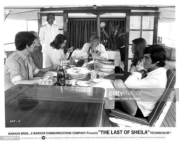 Richard Benjamin, James Mason, Joan Hackett, James Coburn, Raquel Welch and Ian McShane gathered around table in a scene from the film 'The Last Of...