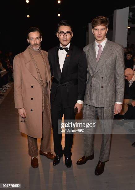 Richard Biedul, Hu Bing and Toby Huntington-Whiteley pose on the front row at the John Lawrence Sullivan show during London Fashion Week Men's...