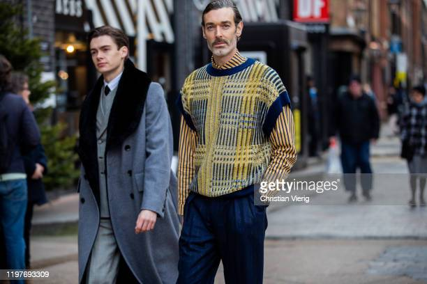 Richard Biedul wearing yellow jumper and Mathias Le Fevre wearing grey belted coat seen during London Fashion Week Men's January 2020 on January 05...