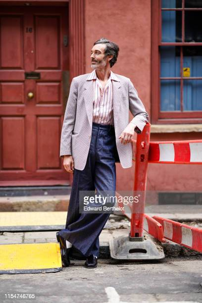 Richard Biedul wears a blazer jacket a striped shirt blue flare pants leather shoes during London Fashion Week Men's June 2019 on June 08 2019 in...