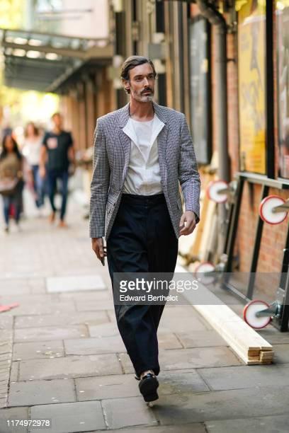 Richard Biedul wears a checked gray blazer jacket, a white shirt, a white t-shirt, black pants, during London Fashion Week September 2019 on...