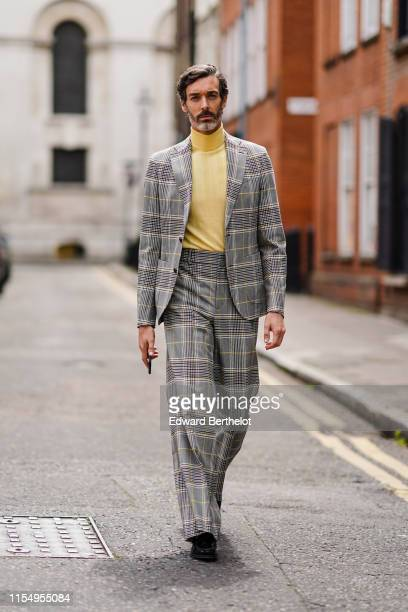 Richard Biedul wears a yellow turtleneck top a checked gray blazer jacket flare pants during London Fashion Week Men's June 2019 on June 09 2019 in...