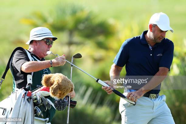 Richard Bland of England and caddy Mick Donaghy on the 18th green during Day One of the Portugal Masters at Dom Pedro Victoria Golf Course on...
