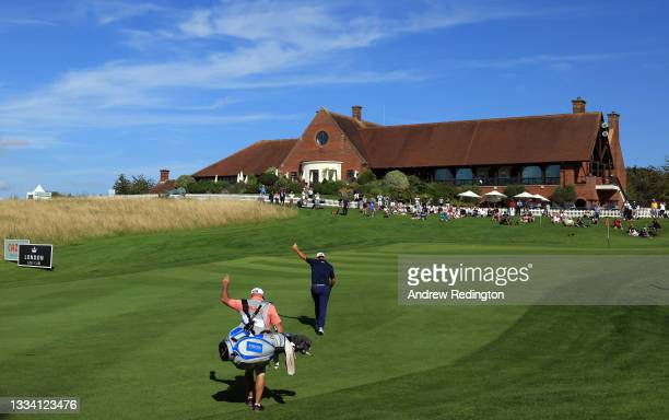 Richard Bland of England and his caddie Davy Kenny acknowledge a shot by a playing partner as they approach the 18th green during the third round of...
