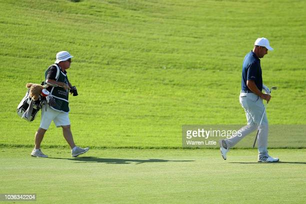 Richard Bland of England walks down the fairway with caddy Mick Donaghy on the 1st hole during Day One of the Portugal Masters at Dom Pedro Victoria...