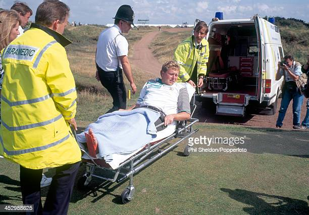 Richard Boxall of Great Britain is taken away by paramedics after breaking his left leg during the British Open Golf Championship held at the Royal...