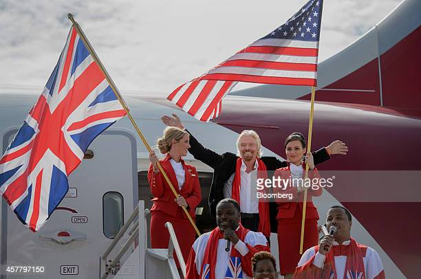 Richard Branson, chairman and founder of Virgin Group Ltd., center, gestures while exiting a Boeing Co. 787 Dreamliner with Virgin Atlantic Airways...