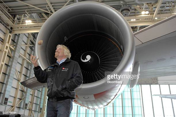 Richard Branson chairman of Virgin Group tosses a babassu nut in the air during a news conference at Heathrow International Airport in London UK on...