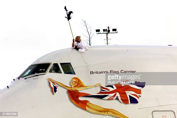 Richard Branson Chairman Virgin Atlantic Airways raises a Nigerian flag 05 July 2001 in excitement as the inaugural flight touches down the Lagos...